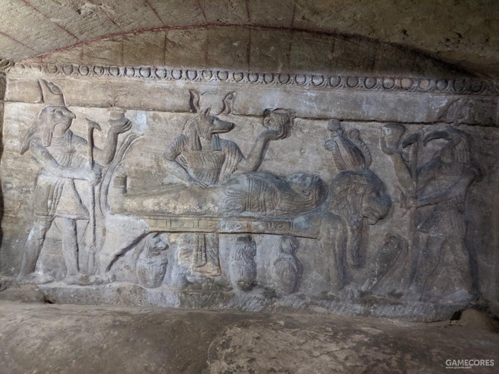 门后的古埃及风格浮雕,从左至右为天神荷鲁斯、死神阿努比斯、书写之神托特(负责评定死者的善恶);木乃伊所躺的狮子床则戴着冥神奥西里斯的帽子