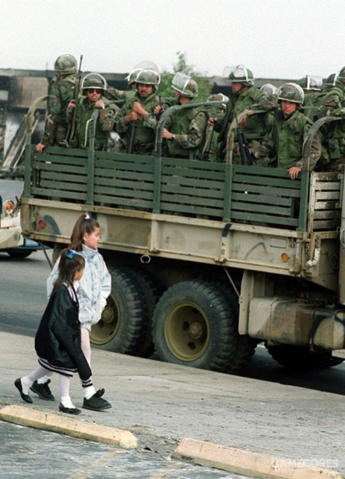 Two girls walk by a truck of National Guardsmen in Los Angeles in 1992. (AP)